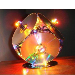 Такой яркий и стильный светильник делается очень просто из компьютерных дисков и елочной гирлянды.