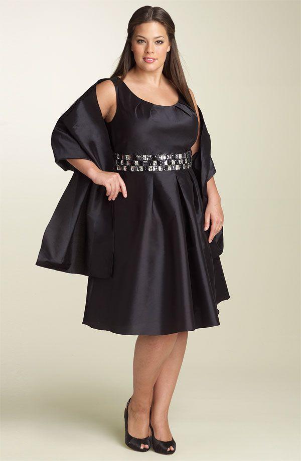 Платье из атласной ткани не самый лучший выбор для дам с пышными формами. В этом случае Платье спасает завышенная талия, драпировка со зрительными вертикальными полосками, пояс, который отвлекает внимание. Платье дополнено накидкой из такой же ткани.