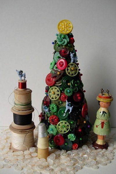 Из пуговиц и других мелких красивых деталей получилась очень необычная елка. Цветные пуговицы на фоне зеленых деталей, словно новогодние игрушки у нарядной елочки.