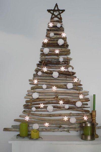 Оригинальная елка из прутиков на стене. Украшают ее снежинки с подсветкой.