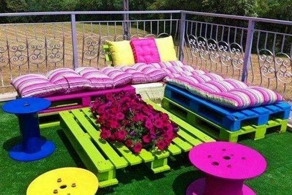 Из поддонов можно соорудить место для отдыха. Стоит только сложить несколько поддонов, выкрасив их в сочные цвета.