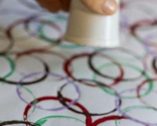 Идея для малышей - рисунки стаканчиком. Для воплощения достаточно вручить чаду в ручки стаканчик и налить несколько красок разных цветов на тарелочки, чтобы было удобно макать.