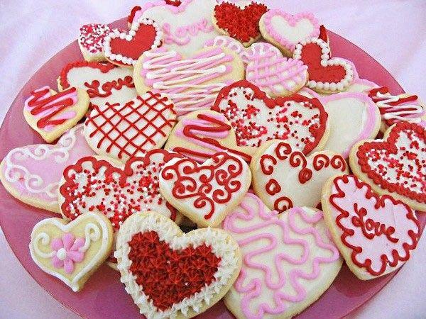 Что за праздник без сладкой выпечки? Приготовьте песочное печенье или пряники в форме сердечек и раскрасьте их красной, белой и розовой глазурью.