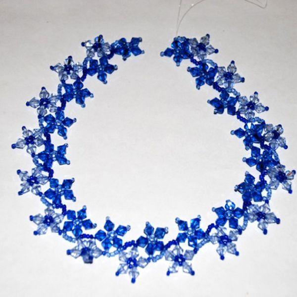Используя голубой и синий стеклянный бисер, можно сплести зимний вариант бус, как на данном фото. Получатся бусы в стиле морозных снежинок.