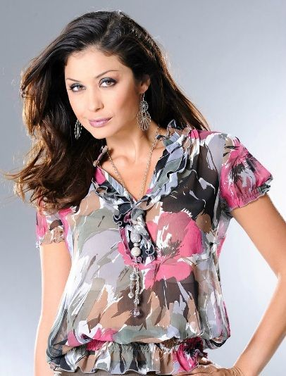 Лёгкая полупрозрачная блузка, которую можно носить как самостоятельно, так и с топом. Особенности модели: маленький воротник-стойка с воланами, а также ступенчатые воланы на самом вырезе.
