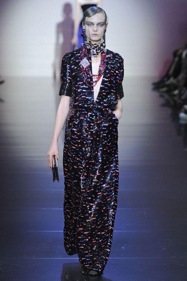 Тёмное платье с мелкой пёстрой абстракцией привлекает внимание глубоким вырезом. Модель имеет короткие рукава с манжетами.