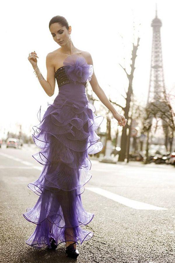 Сиреневое вечернее платье выглядит очень изящно благодаря полупрозрачному лёгкому материалу и привлекающему внимание объёмному цветку на груди.