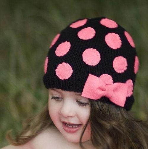 Яркий пример того, как можно сделать оригинальной самую обычную шапку. Цвет кружочков, превращённых в цветочки, и банта хорошо подобраны к цвету лица малышки.