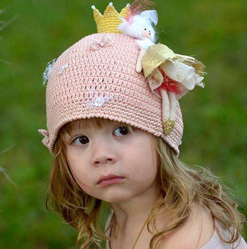 Шапочка для маленькой принцессы. Помимо находящейся на макушке короны, слева она декорирована куколкой.