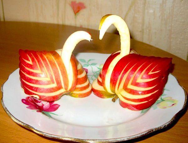 Из яблок многим нравится вырезать лебедей. Их пара, символизирующая вечную любовь, станет отличным украшением любого стола.