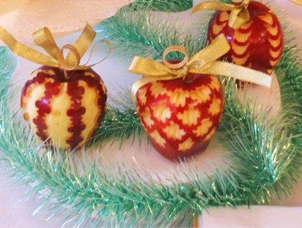 Благодаря карвингу получились интересные новогодние яблоки-шары с узорами. Их дополняют праздничные золотистые ленты.