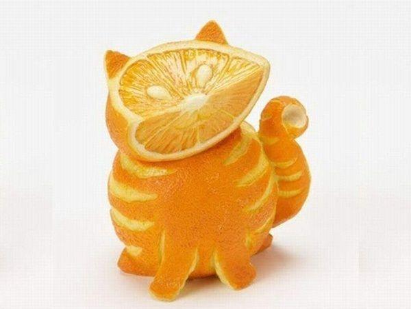 Жизнерадостный полосатый котик с широкой мордочкой и глазками-зёрнышками выполнен из спелого апельсина.