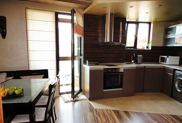 Из-за того, что в этой квартире санузел маленькой площади, стиральная машина стоит на кухне. Пол рабочей зоны визуально отгорожен.