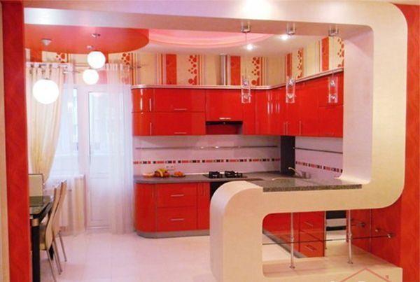 Просторная кухня с балконом выполнена в интересном дизайнерском решении. Насыщенный красный цвет контрастирует с молочным.