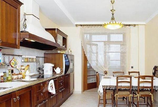 Светлая и просторная кухня с широким выходом на балкон, который закрыт не только дверями, но и лёгким полупрозрачным тюлем.