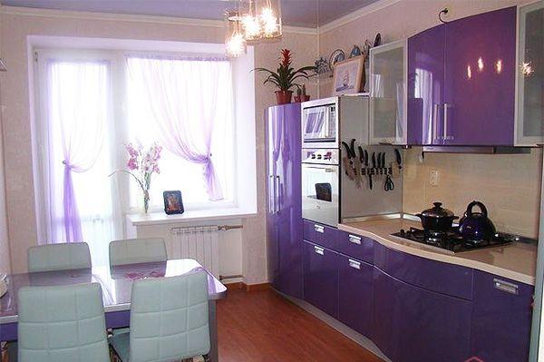Кухня смотрится необычно за счёт довольно редко используемого для оформления гарнитуров сиреневого цвета. Лёгкие занавески подобраны в тон.
