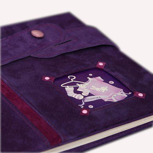 Обложка из натуральной замши фиолетового цвета, декорирована вставками из замши цвета фуксии. Застёжка - хлястик на перламутровой пуговке нежно-розового цвета.