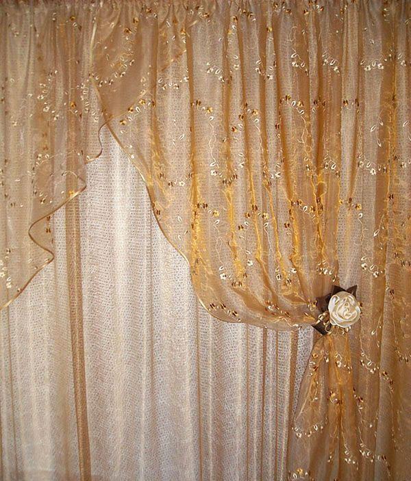 Шторы состоят из двух слоев ткани. Первый слой - белая вуаль, второй - вуаль с вышивкой золотистого цвета. Отделка косой бейкой.
