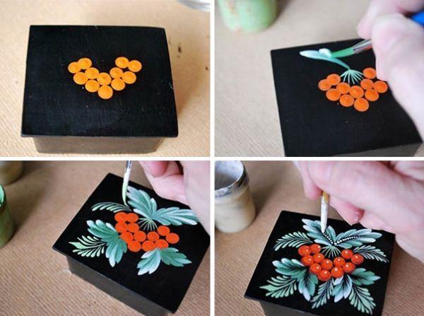Ягоды калины нарисуйте пипеткой. Первую ягоду разместите чуть ниже центра шкатулки. Остальные - полукругом в два ряда. Соберите их вместе тонкой кистью. Для листьев на кисточку наберите сразу две краски. Основную (тёмную) и на кончик кисти (светлую). Нарисуйте травку беличьей кисточкой. Обведите ягоды более тёмным цветом. Нарисуйте прожилки на листьях и поставьте белые точки. Покройте шкатулку лаком.
