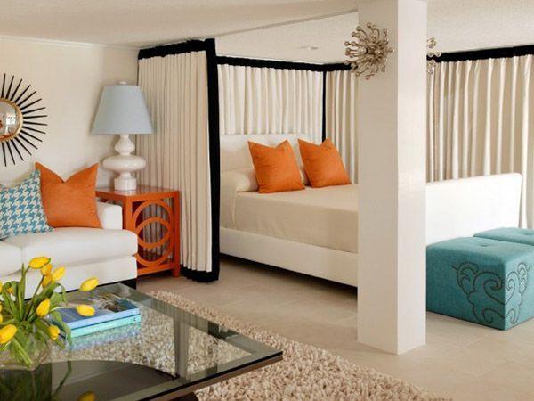 В гостиной оборудовано некоторое подобие алькова. В качестве основных оттенков выбраны пастельные, а яркость придают подушки и пуфики.