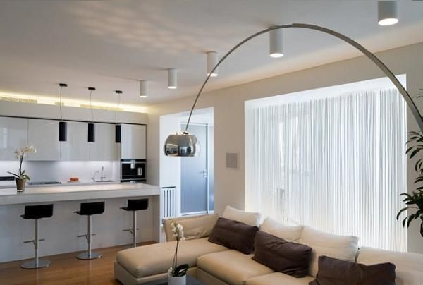 Это уже второй дом. Здесь видно как расположены рядом гостиная и кухня. Очень необычная лампа.