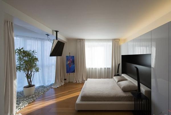 Спальня достаточно просторная и уютная. Шкаф смотрится как часть стены за счет того, что нет ручек на дверцах.