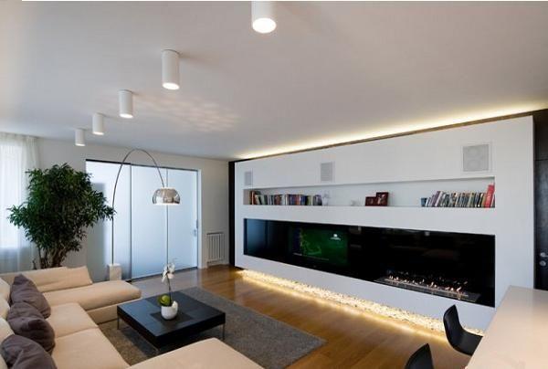 Здесь гостиную можно рассмотреть подробней. Очень удобно в одной стене расположены телевизор, камин и полки для книг.
