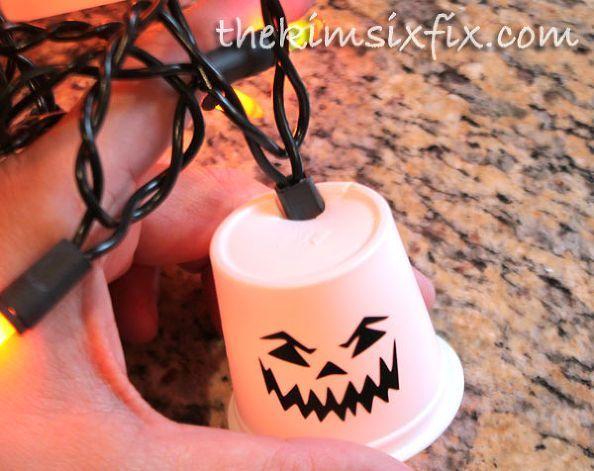 С электрикой без взрослых не справиться, а вот раскрашивать стаканы маркерами под силу даже дошкольникам. Лампочки елочной гирлянды следует просунуть в отверстие на дне стакана.