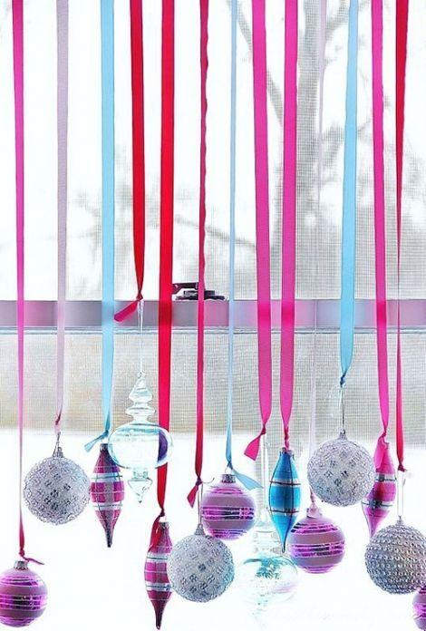Если на вашей елке уже не хватает места, чтобы разместить все игрушки, им можно найти иное применение. Например, с помощью ярких лент украсить стеклянными шарами окно.