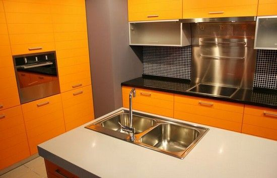 Очень выгодно оранжевая кухня смотрится в окружении стен светло-серого цвета. Стильно и красиво.