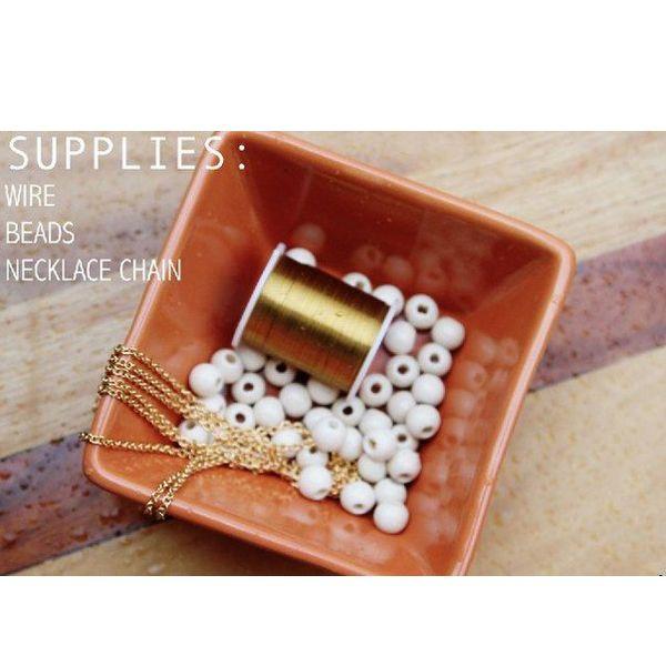 Для работы понадобится: белый крупный бисер, золотистая бисерная проволока, цепочка или шнур (по вашему усмотрению).
