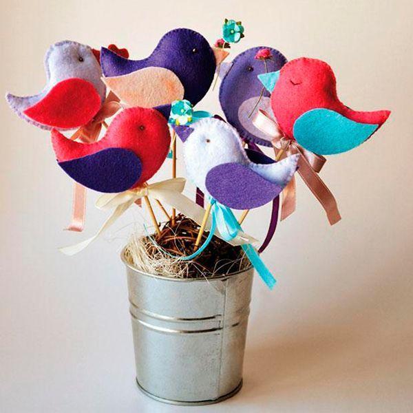 Посаженные на деревянную палочку, птички украсят цветочные горшки или же совьют такое декоративное гнездышко. Для работы нам понадобится: шпажка деревянная, разноцветный фетр, наполнитель, бисер, ленты.