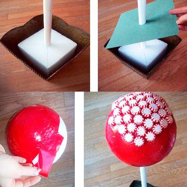 Вставьте стержень в горшочек и обклейте шар красной лентой. Затем с помощью клеевого пистолета приклеивайте конфетки – пользуйтесь пинцетом, чтобы не испачкать сладости.