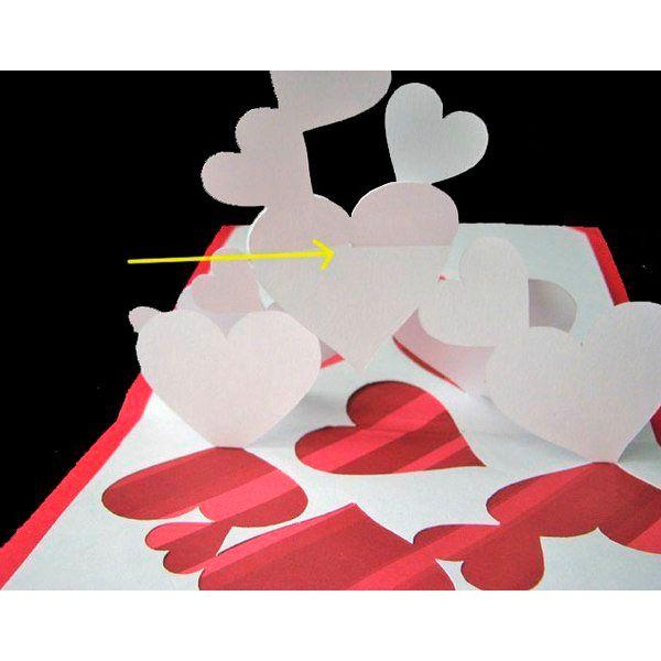 Открытка будет лучше закрываться, если вы отрежете бумагу у центрального сгиба и приклеите их по отдельности к базе (база это плотная бумага красного цвета, которая служит как фон для открытки). Приклейте половинки к базе и соедините сердечки, в которых вы сделали надрезы.