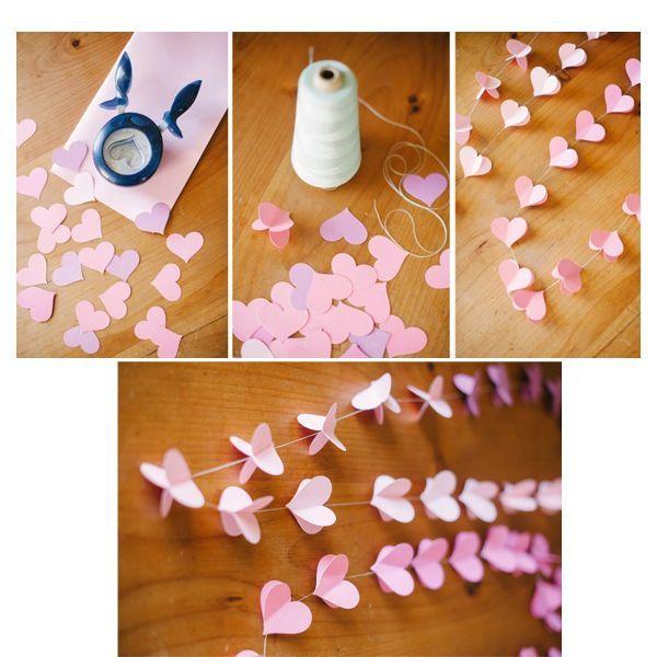Берем цветную бумагу, на обороте рисуем одинакового размера сердца, которые позже нужно будет вырезать. Если от руки не получается сделать одинаковые сердечки, то можно вырезать одно шаблонное, а дальше обводить его и вырезать все остальные. Далее для того, чтобы создать элементы гирлянды, берем два вырезанных сердечка и склеиваем их «спинками», фиксируя нитку между ними.