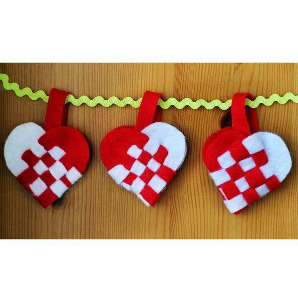 Довольно простая задумка с двухцветными сердцами очень эффектно сможет вписаться в праздничный интерьер ко Дню святого Валентина. Вам понадобятся: войлок, ножницы, нитка, резинка.