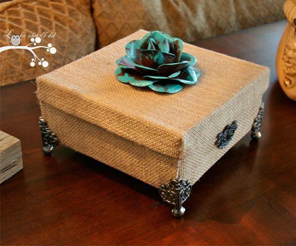 Из небольшой картонной коробки с крышкой можно сделать оригинальную шкатулку. Для этого вам понадобится мешковина и металлическая фурнитура.