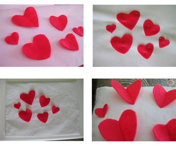 Из фетра вырежьте сердечки разного размера. Расположите их на основе подушки. Пристрочите по центру.