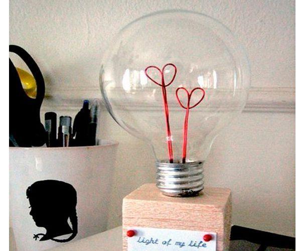 Из старой лампочки можно сделать романтический подарок любимому человеку. Понадобится: проволока красного цвета, деревянный кубик, картон, клей, плоскогубцы, декор на ваше усмотрение.