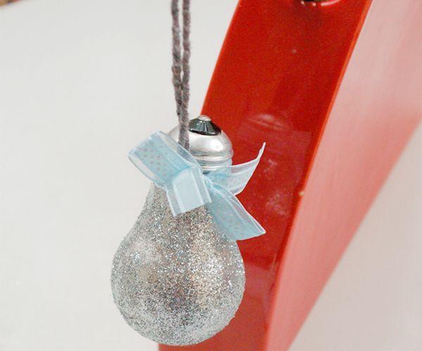 Такую подвеску можно использовать в качестве елочной игрушки или украшения интерьера. Понадобится: лампочка, сухие блестки, клей, шпагат или шнур, лента.