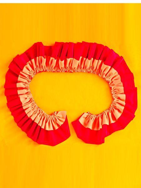 Наложите одну полоску ткани на другую. Прошейте швом вперед иголку, стяните ткань. Нитку с краю закрепите. Длина получившейся оборки должна быть равна окружности плавок.