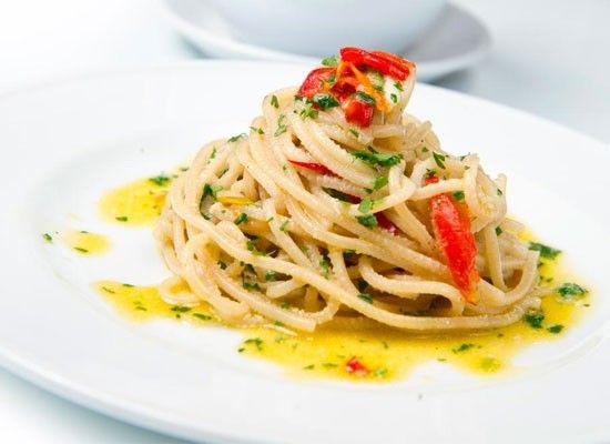 2. На разогретую сковороду налейте оливковое масло. Мелко нарежьте чеснок и чили (предварительно удалив семена). Убавьте огонь до минимума и положите оба ингредиента в масло. Готовьте пару минут, добавьте соль и перец, а также маленький половник воды от варки пасты (или немного горячей воды). Переложите в сковороду пасту и готовьте еще пару минут, постоянно помешивая.