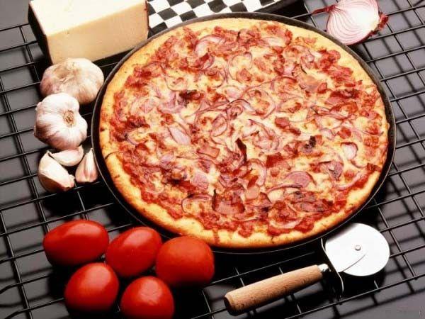 Сладкий перец режем небольшими полосками, ветчину — ломтиками, а салями — полукругом. Намазываем тесто томатным соусом, выкладываем ветчину, салями, перец по кругу и обильно посыпаем сыром.