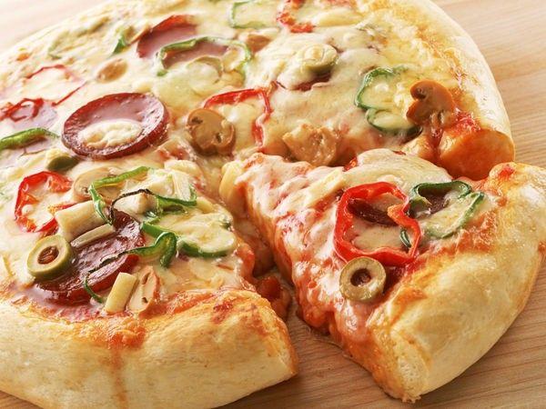 Для хрустящей золотистой пиццы тесто нужно запекать в разогретой до 220-230 градусов духовке около 10-15 мин. По классическому рецепту тесто сначала запекается до полуготовности без начинки 8-10 мин, затем корж нужно достать, выложить начинку, снова поставить в духовку и запечь уже до готовности всей пиццы 5-7 мин.