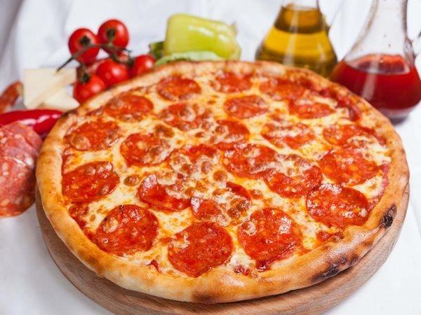 Пицца получится более вкусной, если противень для выпекания немного промазать оливковым маслом и припудрить мукой. Также сбрызнуть маслом необходимо и само тесто сверху – это будет препятствовать намоканию основы при сочной начинке. Если тесто смазывается томатным соусом, то сбрызгивать маслом его не нужно.