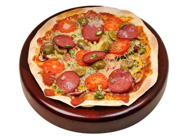 Для пиццы среднего диаметра добавляем не более 3 столовых ложек соуса. В качестве соуса используем не только традиционную томатную пасту, но и нежный сливочный сыр, хумус, кабачковую икру или соус песто. Следим за консистенцией соуса: он не должен быть жидким, иначе тесто поплывет.
