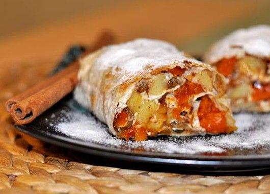 Протушить на сковороде яблоки, курагу и изюм с добавлением сахара и корицы. Выложить начинку на лаваш, свернуть рулетом. Смазать сливочным маслом и запечь в духовке в течение 15 минут.