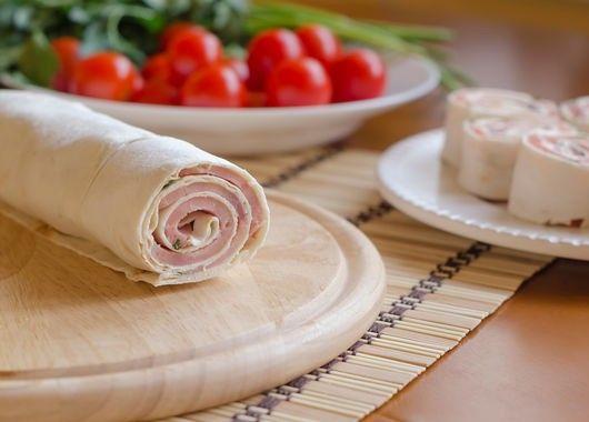 Возьмем 3 листа тонкого лаваша. Каждый из них смазываем соусом из 100 г сметаны и 100 майонеза и мелко нарезанного чеснока. Аккуратно выкладываем ломтики ветчины (на один лаваш понадобится 100–150 г ветчины). Посыпаем мелко нарубленной зеленью на ваш вкус и 300 г тертого сыра. Сворачиваем рулет, заворачиваем его в пищевую пленку и кладем в холодильник на час.