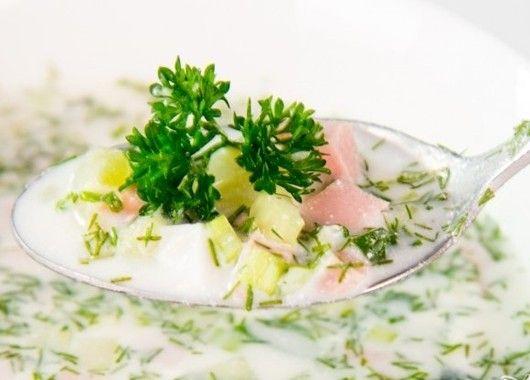 Картофель отварите в мундирах до готовности, яйца отварите вкрутую. Остудите и почистите. Нарежьте кубиками и выложите в большую миску или кастрюлю. Колбасу нарежьте кубиками, добавьте в кастрюлю. Укроп, огурцы и лук промойте, просушите. Зелень измельчите, а огурцы нарежьте кубиками. Если шкурка у огурцов - нежная, то оставьте ее. Все перемешайте в миске, добавив соль, перец и сметану. Залейте ингредиенты сывороткой и еще раз перемешайте.  Остудите и подавайте с долькой лимона.