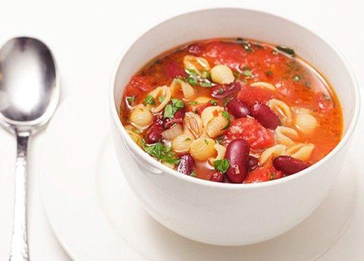 Консервированные помидоры разомните вилкой или руками. В кастрюлю с маслом выложите нарезанные лук и чеснок, орегано (душицу). Обжарьте до мягкости в течение трех минут. Постоянно помешивайте. Добавьте измельченные помидоры в собственном соку, бульон, перец. Перемешайте, повысьте температуру варки. Когда суп закипит, снова снизьте до среднего. Если у вас бульона нет, можно использовать готовый бульонный кубик и кипяченую горячую воду. Варите суп в течение 20 минут, затем добавьте консервированные бобы и макароны. Варите еще столько минут, сколько предписано на пачке с макаронами.